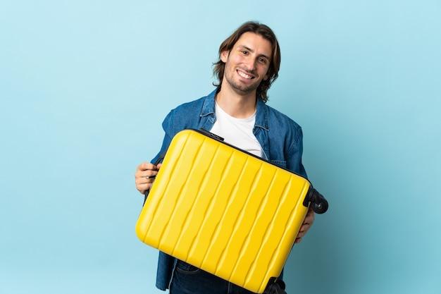 Молодой красавец изолирован на синем в отпуске с чемоданом путешествия