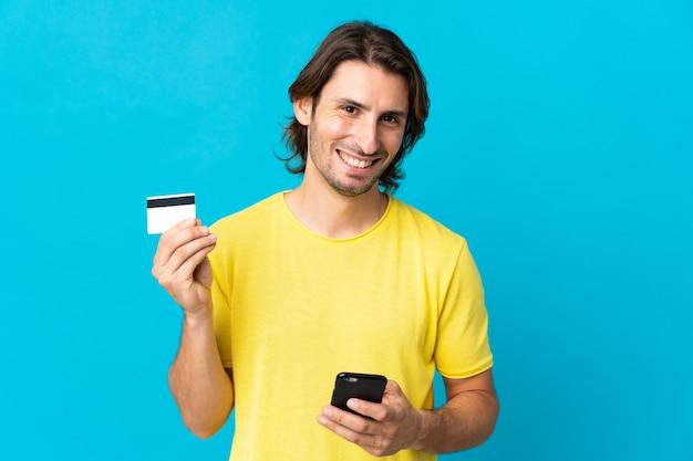 クレジットカードで携帯電話で購入する青い壁に孤立した若いハンサムな男