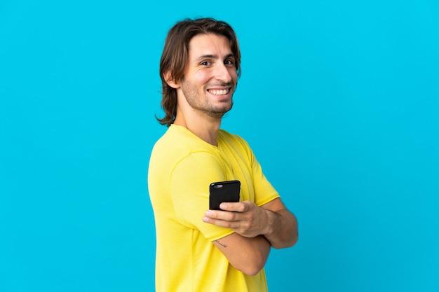 携帯電話を保持し、腕を組んで青い壁に孤立した若いハンサムな男