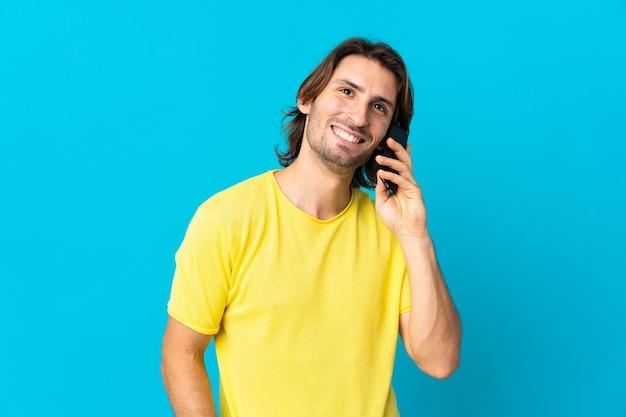 誰かと携帯電話で会話を続けている青い壁に孤立した若いハンサムな男