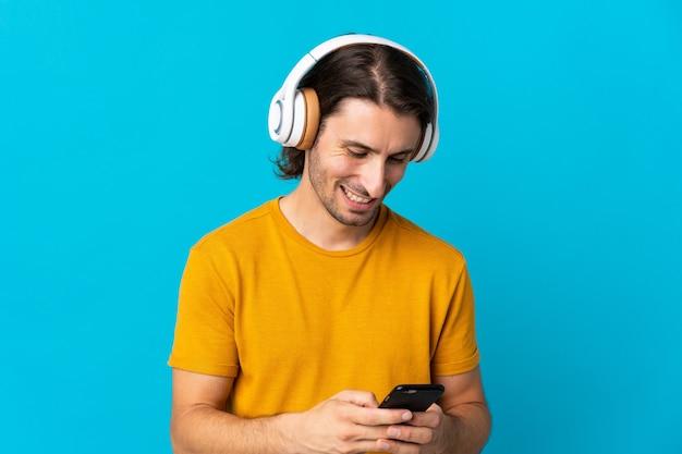 Молодой красавец изолирован на синей стене, слушает музыку и смотрит на мобильный