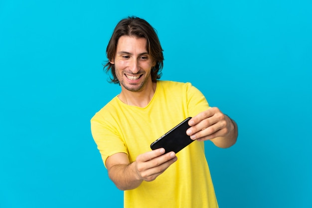 Молодой красавец изолирован на синей стене, играя с мобильным телефоном
