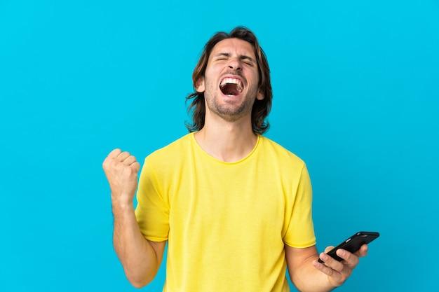 携帯電話を使用して勝利のジェスチャーをしている青い壁に孤立した若いハンサムな男