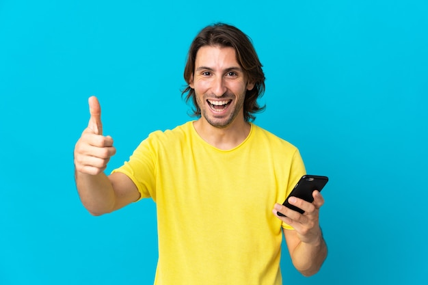 親指を立てながら携帯電話を使用して青い壁に孤立した若いハンサムな男