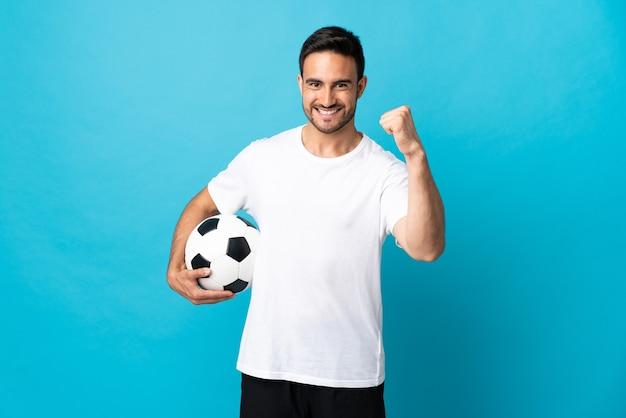 Молодой красавец изолирован на синем с футбольным мячом, празднует победу