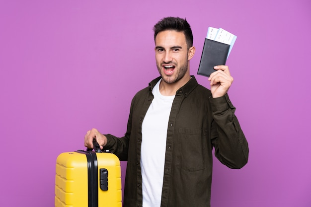 Young handsome man over isolated purple wall in vacation with suitcase and passport
