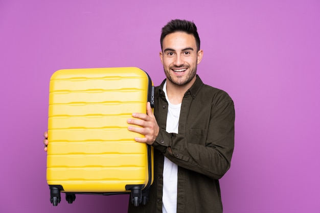 Young handsome man over isolated purple wall in vacation with travel suitcase and surprised