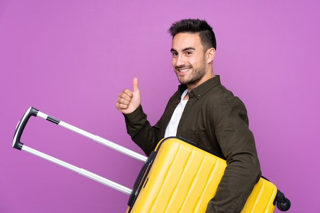 Young handsome man over isolated purple wall in vacation with travel suitcase and with thumb up