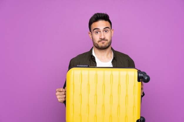 Young handsome man over isolated purple wall in vacation with travel suitcase