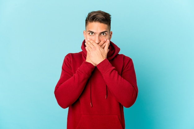 Young handsome man isolated shocked covering mouth with hands