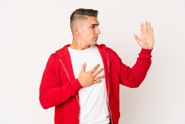 Young handsome man isolated taking an oath, putting hand on chest