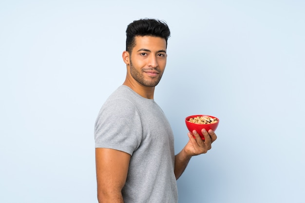 Young handsome man over isolated wall holding a bowl of cereals