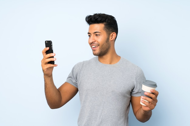 Young handsome man over isolated wall holding coffee to take away and a mobile