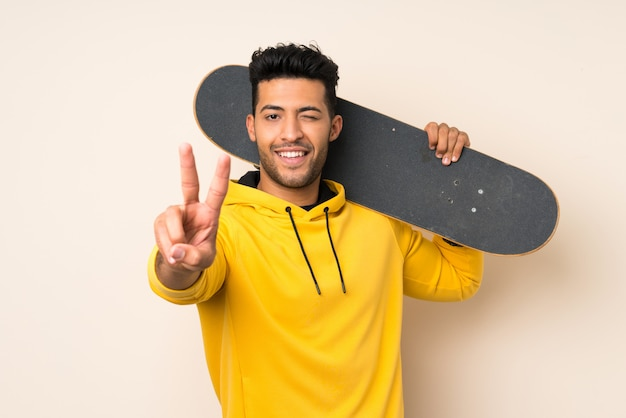 Young handsome man over isolated wall with skate and making victory gesture