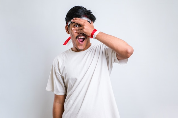 Young handsome man over isolated white background peeking in shock covering face and eyes with hand, looking through fingers with embarrassed expression.