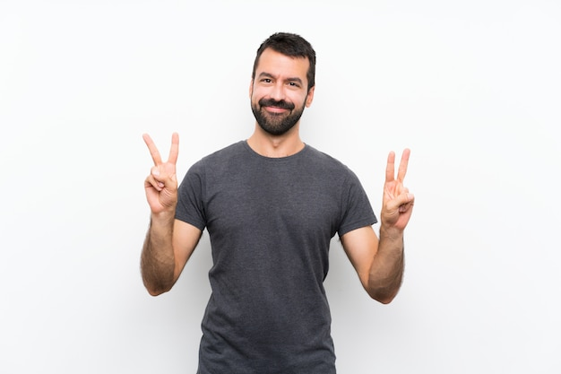 Young handsome man over isolated white background showing victory sign with both hands