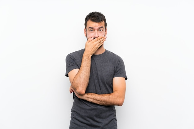 Young handsome man over isolated white wall covering mouth with hands