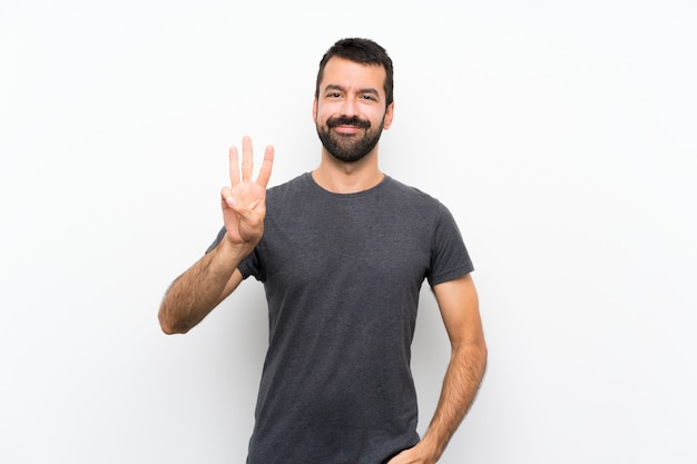 Young handsome man over isolated white wall happy and counting three with fingers