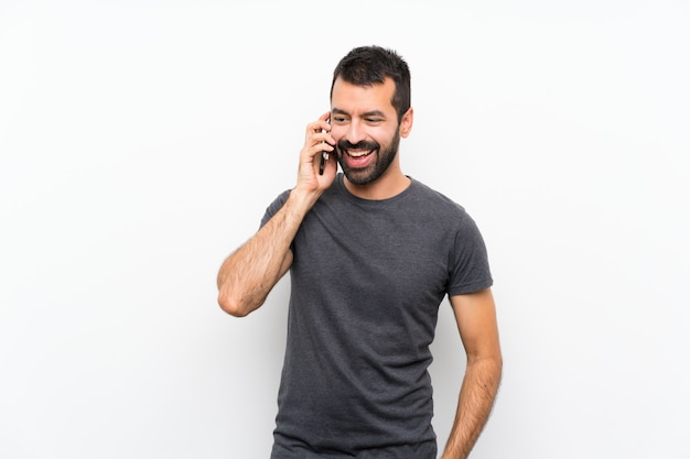 Young handsome man over isolated white wall keeping a conversation with the mobile phone