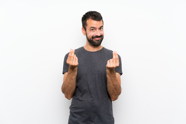 Young handsome man over isolated white wall making money gesture