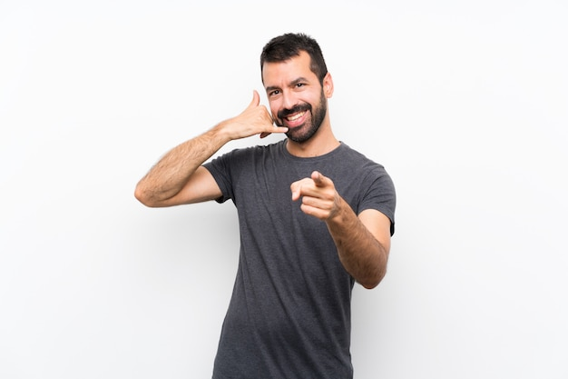 Young handsome man over isolated white wall making phone gesture and pointing front