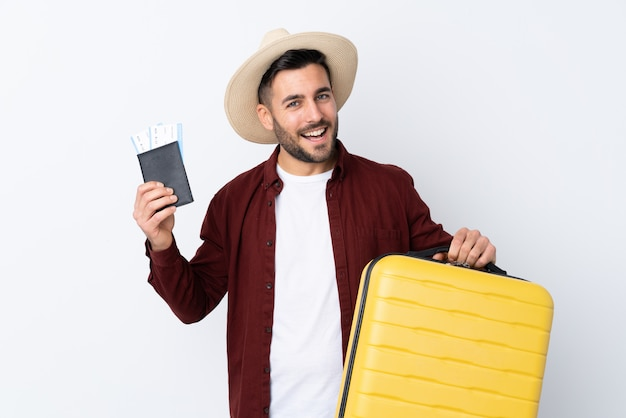Young handsome man over isolated white wall in vacation with suitcase and passport