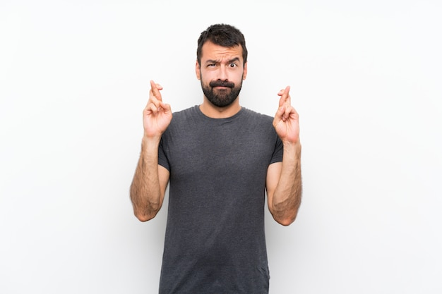 Young handsome man over isolated white wall with fingers crossing and wishing the best