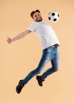 Молодой красавец прыгает с футбольным мячом