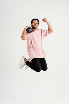 スピーカーでジャンプする若いハンサムな男 Premium写真