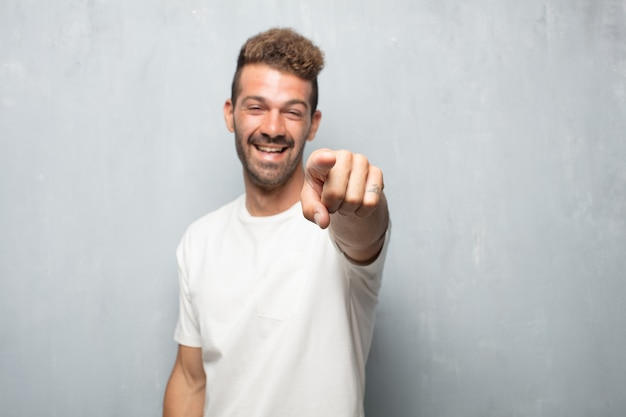 Young handsome man laughing hard at something hilarious and pointing towards you