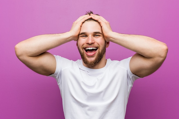 Young handsome man laughs joyfully keeping hands on head