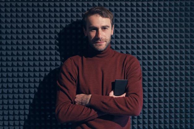 Молодой, красивый мужчина, прислонившись к серой стене со скрещенными руками. улыбающийся мужчина, глядя на камеру, держа телефон. игра света и тень