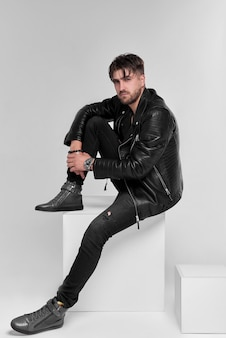 Young handsome man, leather jacket on naked torso, emotional posing, grey wall, modern guy.