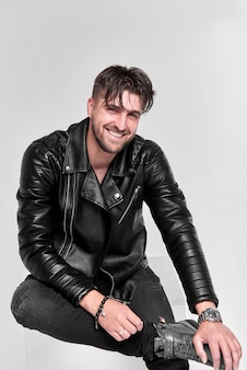 Young handsome man, leather jacket on a naked torso, sitting and smiling, emotional posing, gray wall, modern guy.
