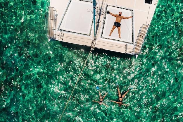若いハンサムな男は、インド洋モーリシャス島のヨットに横たわっています。
