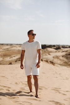 Young handsome man in light clothing and sunglasses in the desert. concept of freedom relaxation