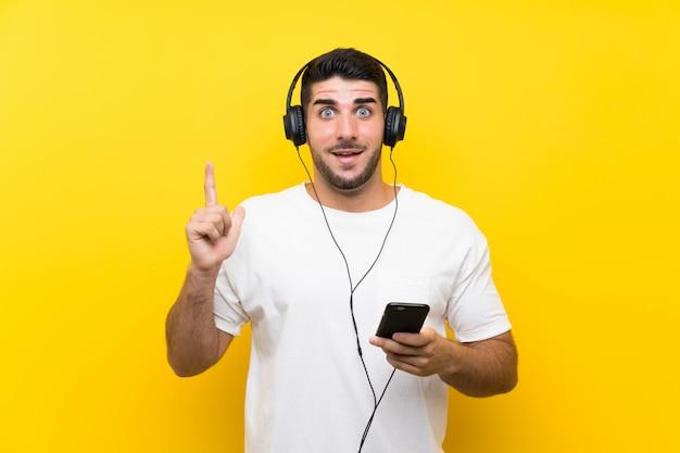 素晴らしいアイデアを指している孤立した黄色の壁を越えて携帯電話で音楽を聴く若いハンサムな男