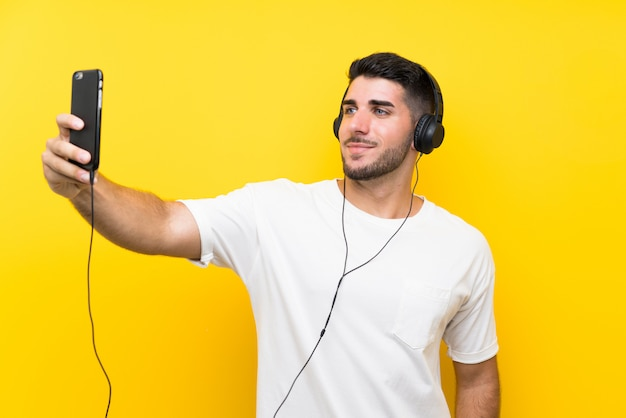 Young handsome man listening music with a mobile over isolated yellow wall