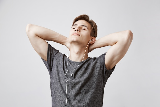 Young handsome man listens music with earphones
