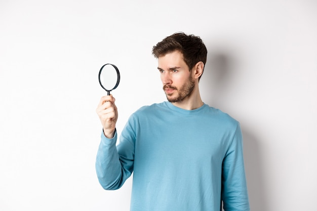 젊은 잘생긴 남자는 흰색 배경에 서서 호기심 많은 얼굴로 돋보기를 통해 조사하거나 무언가를 찾고 있습니다.