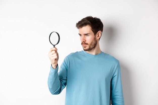 젊고 잘생긴 남자는 흰색 배경에 서서 호기심 많은 얼굴로 돋보기를 통해 무언가를 조사하거나 검색합니다.