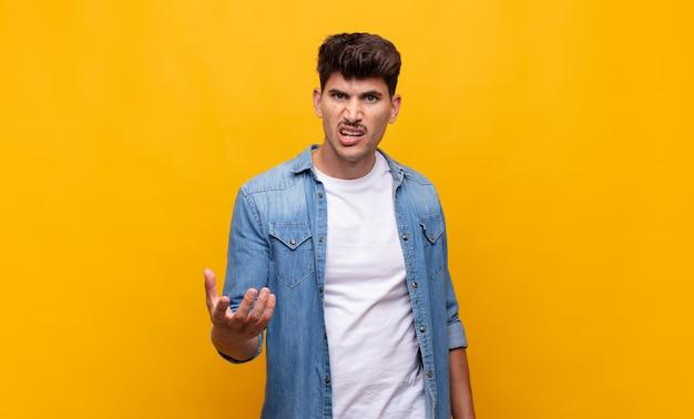 Молодой красивый мужчина выглядит сердитым, раздраженным и расстроенным, кричит, черт возьми, или что с тобой не так