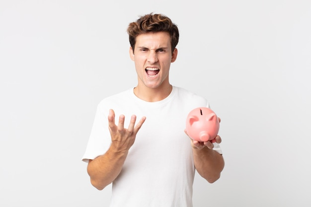 Young handsome man looking angry, annoyed and frustrated and holding a piggy bank