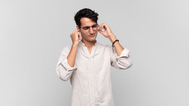 怒り、ストレス、イライラしているように見える若いハンサムな男は、耳をつんざくような音、音、または大音量の音楽で両耳を覆っています