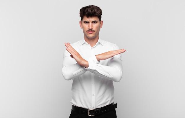 イライラしてあなたの態度にうんざりしているように見える若いハンサムな男は、十分に言っています!手を前に交差させて、やめるように言った
