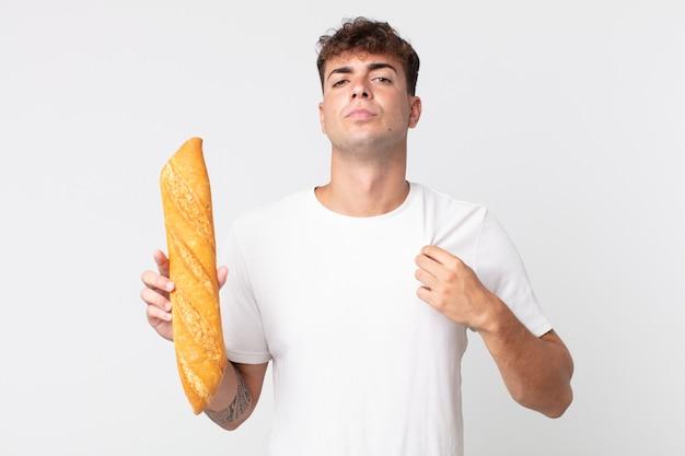 傲慢で、成功し、前向きで、誇りに思って、パンのバゲットを持っている若いハンサムな男
