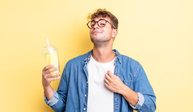 Молодой красавец выглядит высокомерным, успешным, позитивным и гордым. концепция молочного коктейля