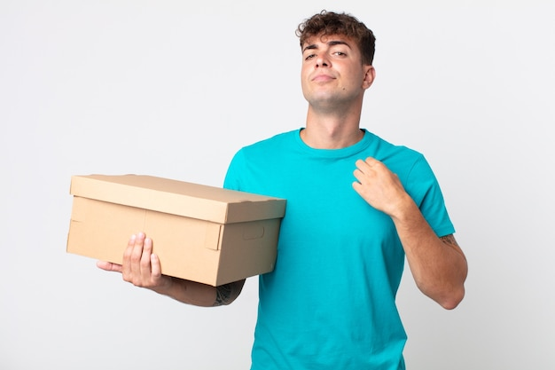 Young handsome man looking arrogant, successful, positive and proud and holding a cardboard box