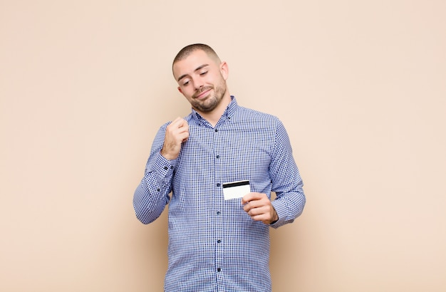 Young handsome man looking arrogant, successful, positive and proud, pointing to self with a credit card