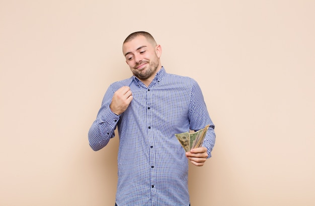 Young handsome man looking arrogant, successful, positive and proud, pointing to self with dollar banknotes